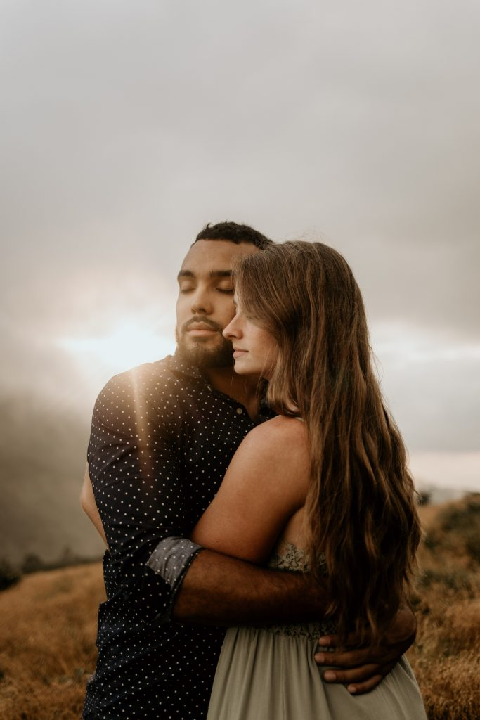 couple hugging on roan mountain with clouds