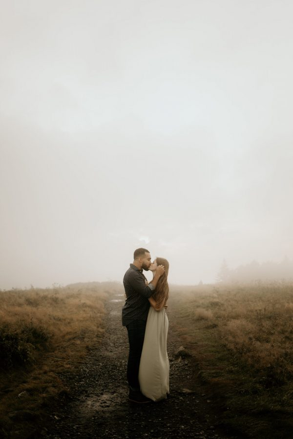 couple standing together hugging on mountain rainy and foggy